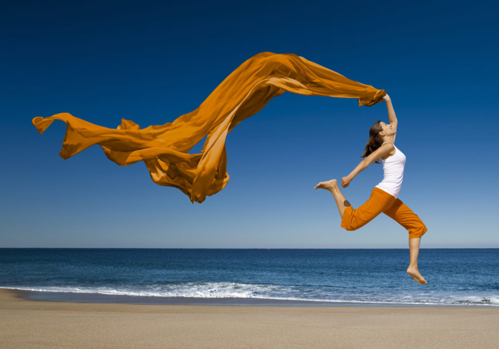 A woman wearing orange pants and a white top is on a beach.  The water is blue.  The woman jumps into the air, and she kicks her right leg behind her.  She has an orange scarf in her left hand, and it floats above and behind her against a blue sky.