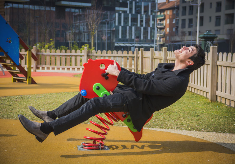 37873394 - young man reliving his childhood plying in a childrens playground riding on a colorful red spring seat with a happy smile in an urban park