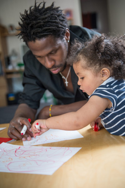 a father playing and drawing with his daughter